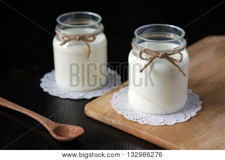 natural yogurt in a jar on the dark background