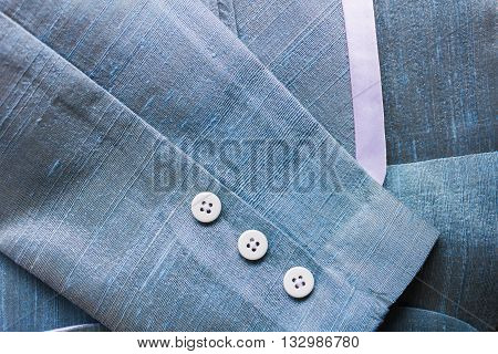 Blue silk cloth texture pattern background from silk suit with simply white botton