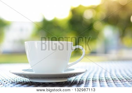 Coffee cup on the table with blur green nature background