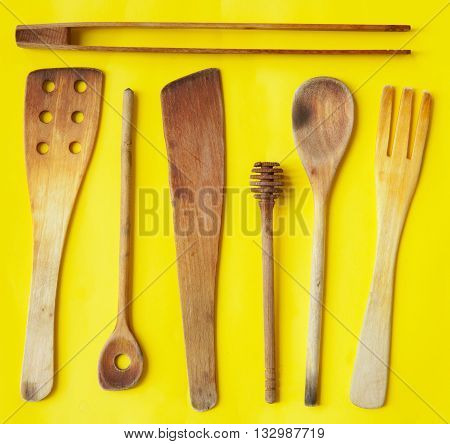 Old wooden spoons and stirrers on yellow background kitchen utensils