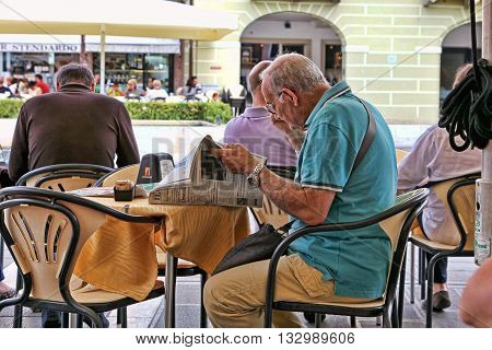 VENICE MESTRE-June 29 2014. Elderly man reading a newspaper in the cafe on Piazza Erminio Ferretto in Italy. Mestre is the most populated urban area of the mainland of Venice part of the territory of the city of Venice in Veneto Italy.