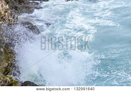 Waves breaking on rocky coast. Splashes on a background of stones.