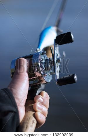 Male hand on a spool of a round fishing reel attached to a fishing rod with fishing lure and blurred nature background.