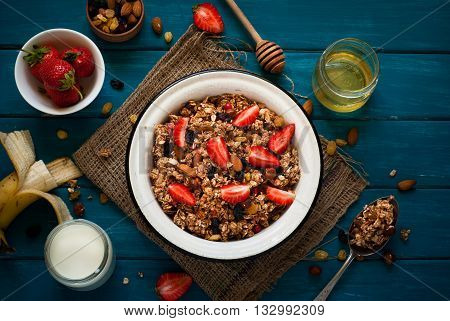 Granola. Granola with yogurt, honey and berries on blue wooden table.