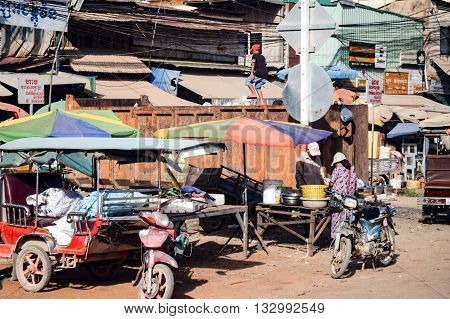 Cambodia - November 22, 2014: Local Cambodian street scene showing boys climbing and playing on a large rubbish bin