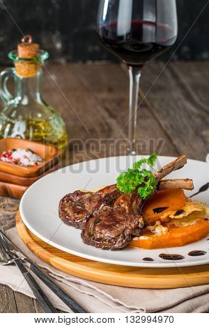 Roasted lamb ribs with  grilled pumpkin and sause on white plate with red wine and seasonings