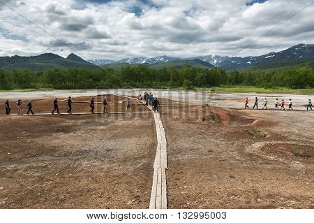 NALYCHEVO KAMCHATKA RUSSIA - JULY 30 2014: Tourists walk on wooden deck overlooking Thermal Pad Boiler or Travertine Shield Boiler with sleep and active griffins (mud pot) with thermal water.