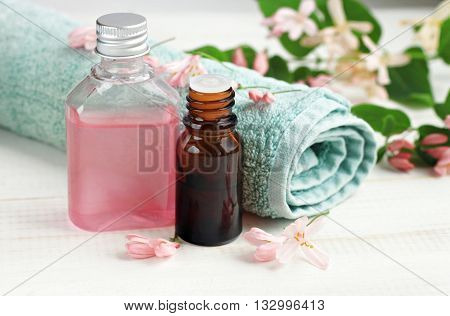 Botanical cosmetic product. Pink tonic facial wash, essential oil, bathroom towel, fresh flowers. Herbal spa.