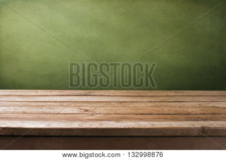 Background with wooden deck tabletop and grunge green wall
