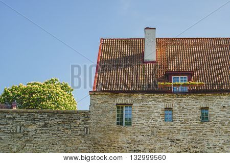 Medieval stone house facade. Red tile roof and mansard window with flower pots.