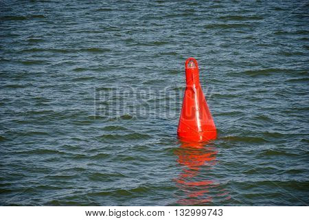 Floating red navigational buoy on blue water