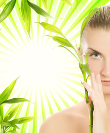 image of beautiful young woman  - Beautiful young woman with bamboo plant over abstract green background - JPG
