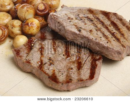 Chargrilled rump steaks with sauteed button mushrooms.