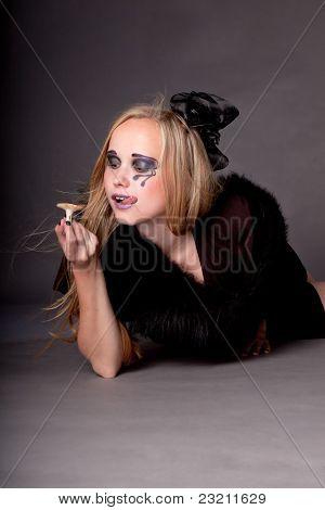attraktive Mädchen Make-up für Halloween isst Pilze