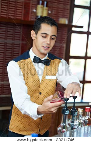 Cheerful arab barman in uniform preparing cocktail in his hand