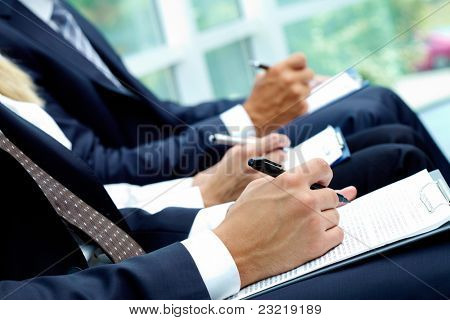 Close-up of business people hands with papers writing at lecture