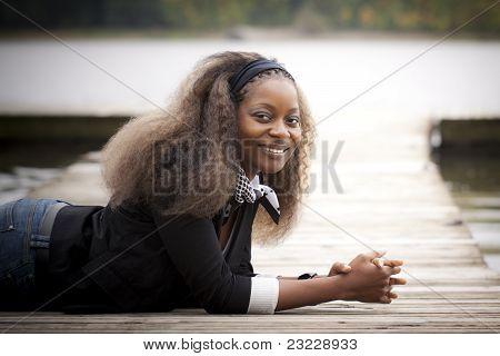 African woman lying on quay