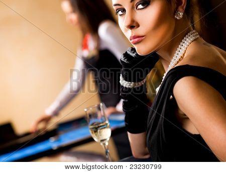 Beautiful elegant female sitting in casino with glass of wine