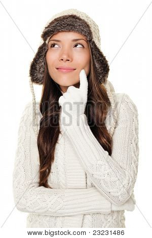 Thinking winter woman looking pensive to the side and up wearing warm winter clothing - sweater and tuque wool cap. Happy smiling woman isolated on white background. Asian Caucasian female model.
