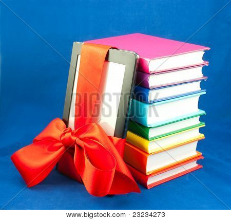 Electronic book reader tied up with red ribbon and stack of books