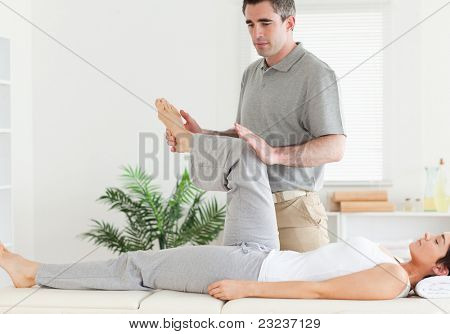 A chiropractor is stretching a customer's leg