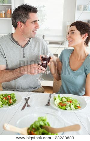 Close up of a Happy couple toasting with redwine in a dining room