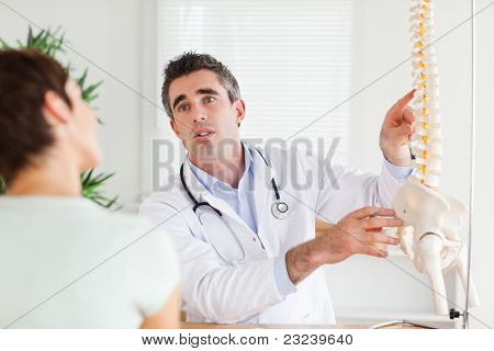 Male Doctor explaining something to a woman in a room