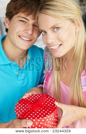 Teenage boy giving gift to girl