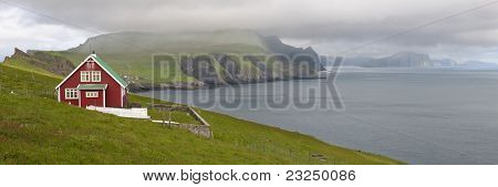 Red farmhouse on coast of Mykines, Faroe Islands