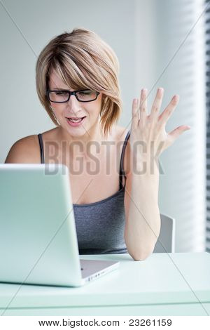 oung businesswoman showing annoyance over a problem while working on her laptop (color toned image)