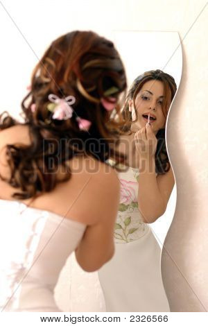 Bride Applying Make Up In Mirror