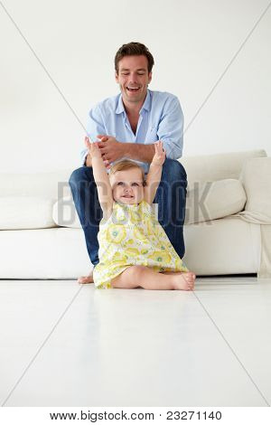 Doting father with baby daughter at home