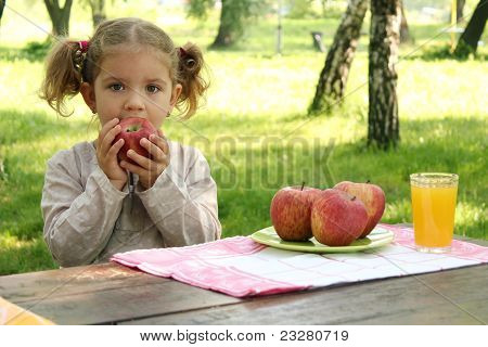little girl eat fruit in park