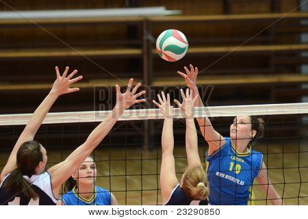 KAPOSVAR, HUNGARY - APRIL 24: Szandra Szombathelyi (10) strikes the ball at the Hungarian NB I. League woman volleyball game Kaposvar (blue) vs Ujbuda (black), April 24, 2011 in Kaposvar, Hungary.