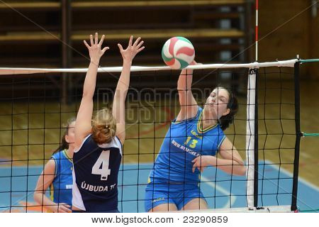 KAPOSVAR, HUNGARY - APRIL 24: Gabriella Kondor (R) strikes the ball at the Hungarian NB I. League woman volleyball game Kaposvar (blue) vs Ujbuda (black), April 24, 2011 in Kaposvar, Hungary.
