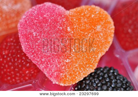 closeup of a heart shaped candy in a tray full of candies