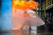 Firemen Using Water From Hose For Fire Fighting At Firefight Training Of Insurance Group. Firefighte poster