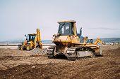 Industrial Motor Grader And Backhoe Excavator On Highway Construction Site poster