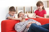 Little children painting their fathers face while he sleeping. April fools day prank poster