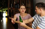 Young man refusing to give bottle of beer to woman in bar. Alcoholism problem