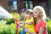 Happy Mother And Child Daughter Watering In Domestic Garden poster