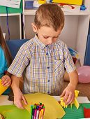 Small students boy painting in art school class. Child drawing by paints on table. Portrait of littl poster