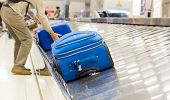 Blurry Picture Of Suitcase On Luggage Conveyor Belt At Baggage Claim At Airport. Lines Of People Wai poster