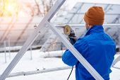 Rearview Shot Of A Professional Electricity Technician Installing Solar Panels Outdoors In Winter Co poster