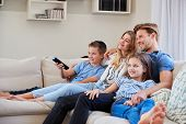 Family Sitting On Sofa At Home Watching TV Together poster