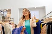 shopping, fashion, sale and people concept - happy young woman with clothes on hangers in mall or cl poster