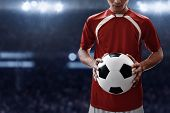 Soccer Player Holding Soccer Ball On The Field poster