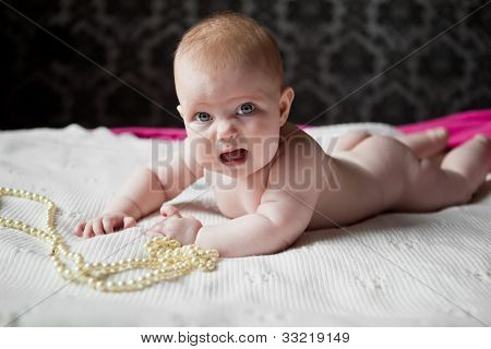 Cute Little Girl Infant Lying On The Rug With Pearl Beads And Weeps