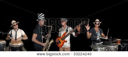 Portrait of four musicians playing isolated against black background