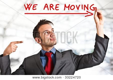 "Friendly businessman writing ""We are moving""on the screen"